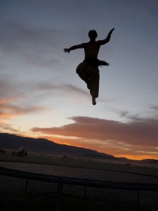 Photo takend of trampoline jump on beach at sunset.