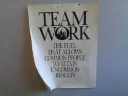 "Sign posted on office wall with these words: ""Team Work: The fuel that allows common people to obtain uncommon results."""