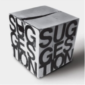 "Image is of a square cardboard box with the word ""suggestion"" written on the two visible sides."