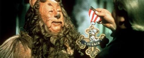 "The photograph is an image of a character known as The Cowardly Lion from the movie ""Wizard of Oz."" In this photograph, the Lion is being presented a medal that includes red gems and the word ""Courage"" in a gold setting, as the Wizard recognizes the Lion for having courage of the heart to act in new ways in the world."